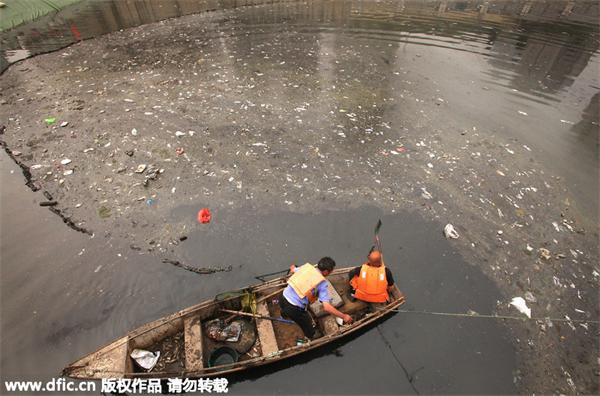 Chinese workers clean a heavily polluted canal running through central Beijing on May 16, 2010. [Photo/IC]