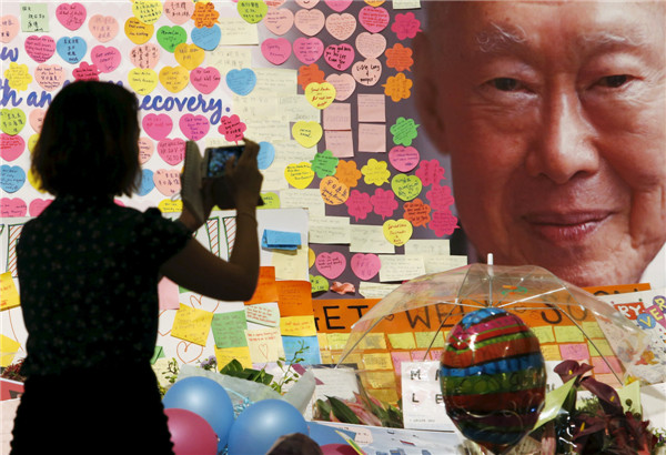 A woman takes photos of cards for former Singaporean prime minister Lee Kuan Yew, placed at a well-wishing corner at the Singapore General Hospital in Singapore, March 23, 2015. [Photo/Agencies]