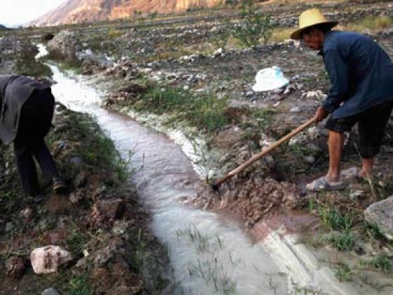 Farmers dig ditches to lead water from a polluted stream into farm fields, in Dongchuan district of Kunming, Yunnan province. Photo: Reuters